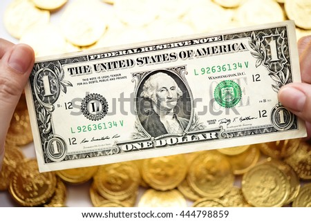 One dollar on hand and gold coins for background