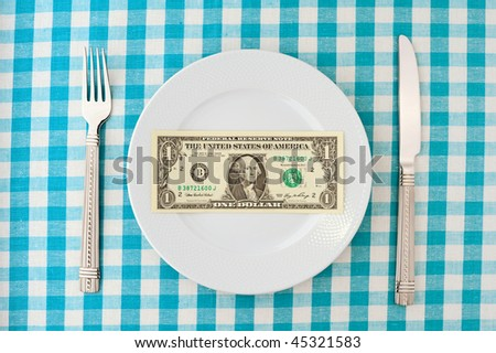 One dollar on plate with fork and knife on checked blue tablecloth