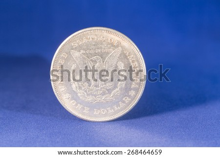 One dollar silver coin with blue background - stock photo
