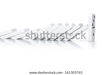 One domino resisting the pressure of all the others, standing out from the crowd - stock photo