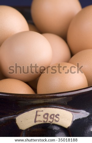One dozen eggs packed in pottery bowl - stock photo