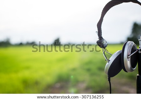 One earphone at green field in thailand