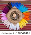 One egg in a basket on iridescent feathers - stock photo