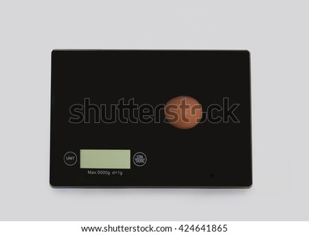 One egg on a digital white kitchen scale. (weighing products) - stock photo
