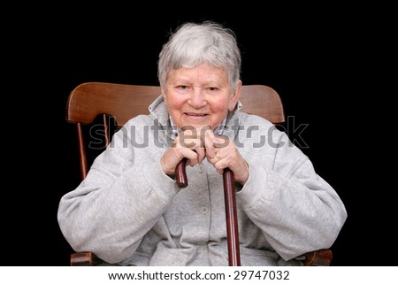 one elderly adult female sitting in a rocking chair holding her cane - stock photo
