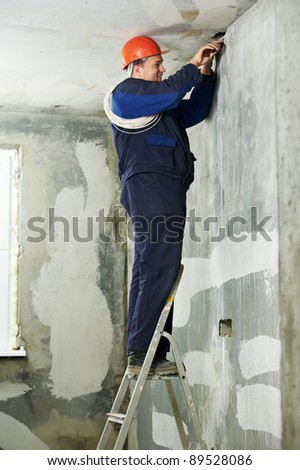 One electrician at work laying wiring cable