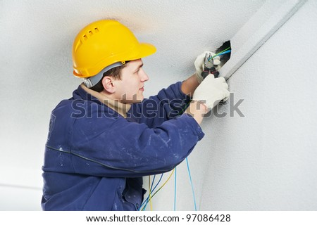 One electrician at work laying wiring cable - stock photo