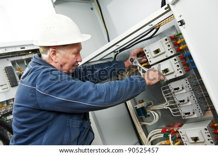 One electrician at work with wrench spanner tighten the screw in electical box
