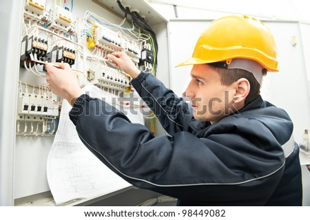 One electrician builder at work with assembly drawing inspecting high voltage power electric line distribution fuseboard - stock photo