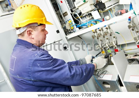 One electrician builder at work with tester measuring high voltage of power electric line in electical distribution fuseboard