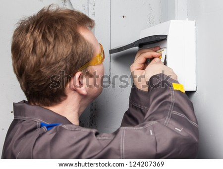 One electrician examining fuse box - stock photo