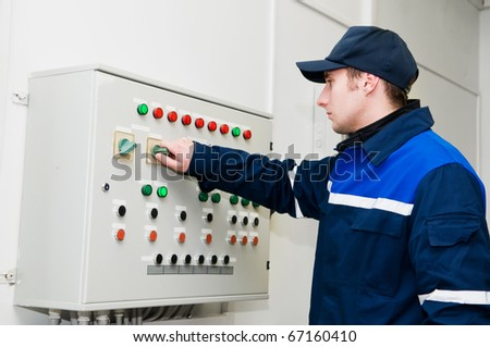 One electrician working on a industrial panel adjusting voltage by toggle switch