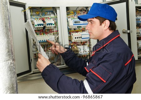One electrician working on a industrial panel checking and inspecting new wiring at fusebox - stock photo
