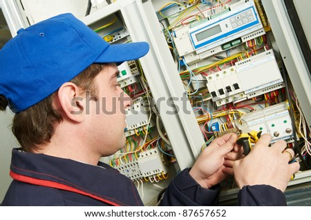 One electrician working on a industrial panel mounting and assembling new wiring - stock photo