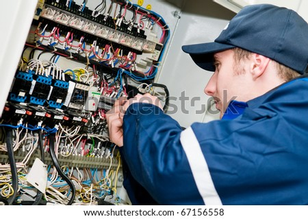 One electrician working on a industrial panel mounting, assembling, adjusting new voltage wiring - stock photo