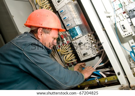 One electrician working on a industrial voltage panel mounting and assembling new wiring - stock photo