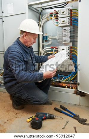 One electrician working with new electical box wiring and drawing - stock photo