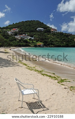 One empty chair sits on a tropical beach - stock photo