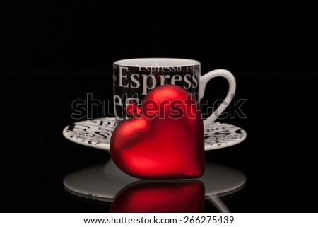 One empty coffee cup and red heart on a black glass desk - stock photo