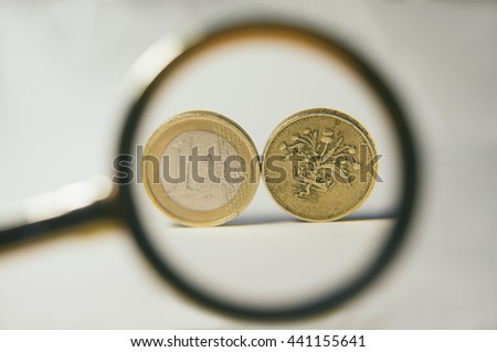 one Euro and one Pound coins stand under a magnifying glass - stock photo