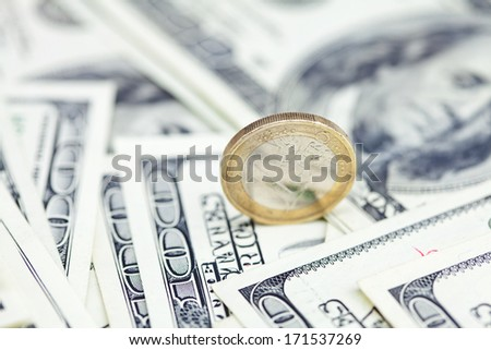 one euro coin against the dollar banknotes - stock photo