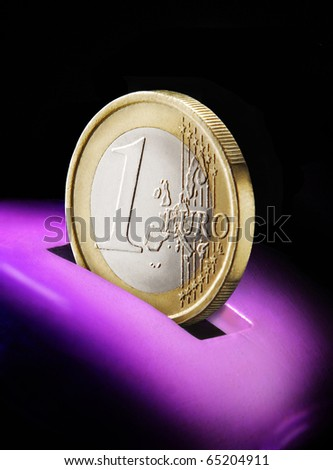 One euro coin and piggy bank isolated on black background. - stock photo