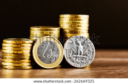 one euro coin and us quarter dollar coin and gold money on the desk - stock photo