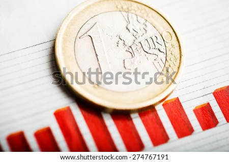 One euro coin on fluctuating graph. Rate of euro (shallow DOF)  - stock photo