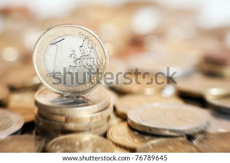 one euro coin on pile of euro coins in background