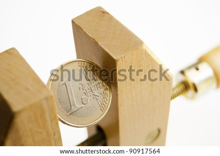 One euro coin under pressure in  a wooden clamp - stock photo