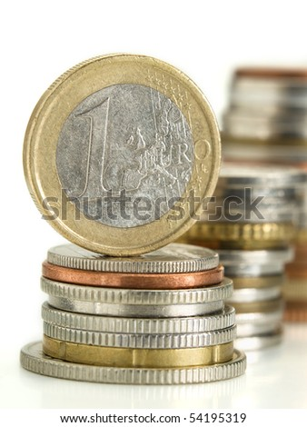 one euro money coin on top of the stack of coins over white background , shallow DOF, useful for various finance related themes