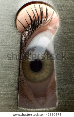 One eye looking through a keyhole close up shoot - stock photo