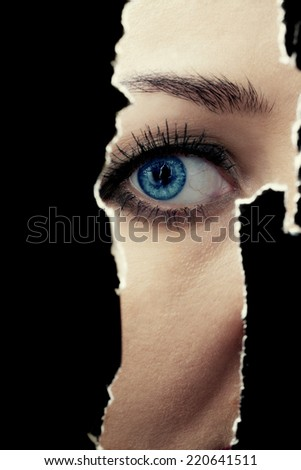 One eye of a young woman spying through a hole in the wall - stock photo