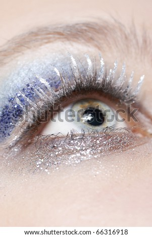 One female eye with blue eyeshadow and silver sparkle make-up