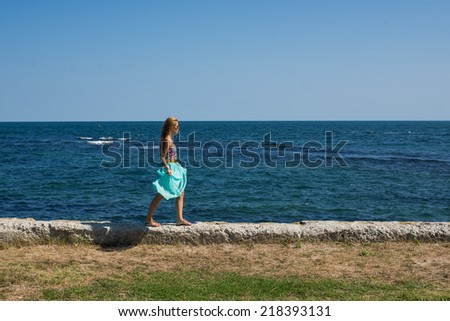one female walking at the port, near by the sea, blue sky