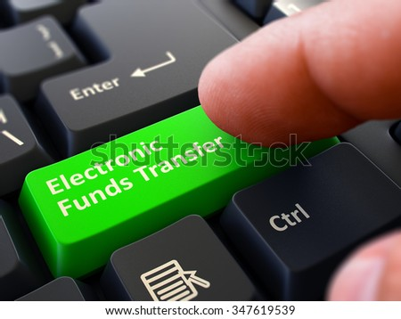 One Finger Presses Green Button Electronic Funds Transfer on Black Computer Keyboard. Closeup View. Selective Focus. - stock photo