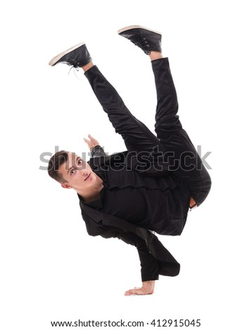 One fit handsome modern style dancer young man working out, performing breakdance moves, hand stand on the floor. - stock photo