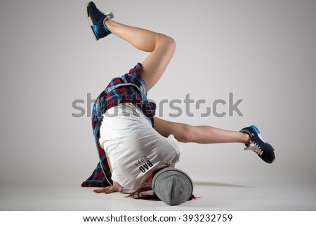 One fit young woman wearing casual plaid shirt performing breakdance moves on the floor. Modern style beautiful teen dancer working out, dancing. Full length image, studio gray background, back view - stock photo