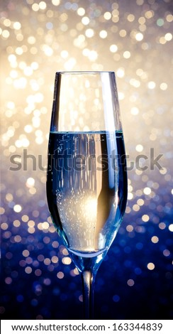 one flute of champagne on blue and white bokeh background - stock photo