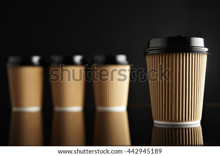 One focused coffee take away cardboard paper cup ahead others unfocused, all closed with black caps presented on black and mirrored. Retail mockup presentation - stock photo