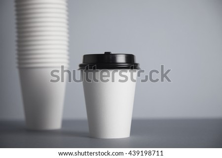 One focused take away white paper cup with black cap presented in front of unfocused group of other cups folded one in other in big bunch, isolated on simple gray background - stock photo
