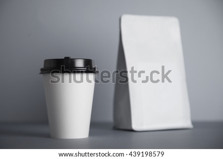 One focused take away white paper cup with black cap presented near blank white bag, isolated on of simple gray background - stock photo