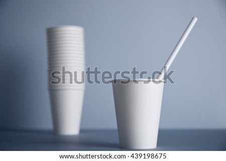 One focused take away white paper cup without cap with drinking straw inside presented in front of unfocused group of other cups folded one in other in big bunch, isolated on simple gray background - stock photo