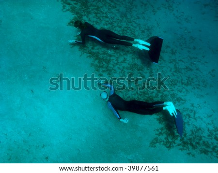 One freediver takes photo of another at the sand bottom of the Red Sea - stock photo
