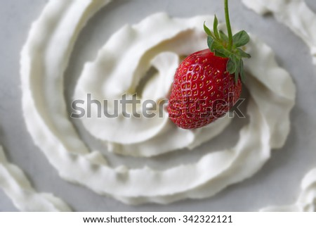 One fresh and juicy strawberry placed at the center of a swirl of whipped cream. The cream has been put slightly out of focus on purpose so the strawberry appears to be coming out of the photo. - stock photo