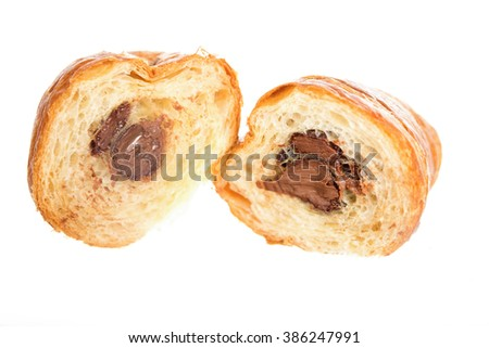 One fresh and tasty croissant with chocolate on plate isolated on white background. Breakfast concept, easy and fast junk food. Cross in half, see the delicious chocolate - stock photo