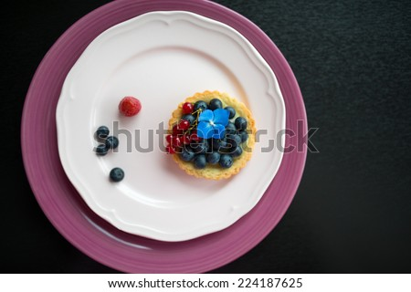 One fresh cake with blueberries and redcurrants on the plate - stock photo