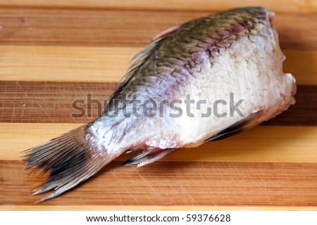 One fresh fish on a chopping board. - stock photo