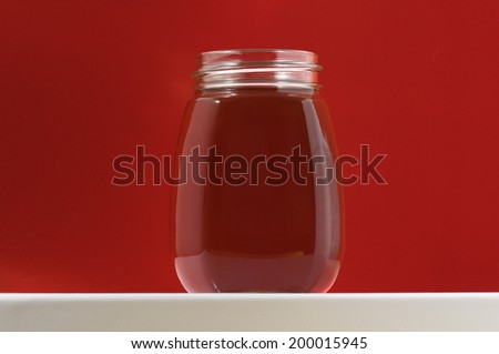 One Full Honey Jar on a Colored Background