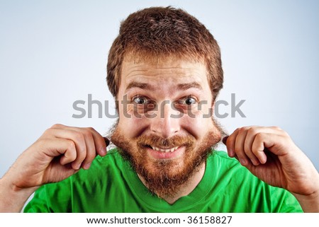 One funny silly man grabbing his hairy beard - stock photo